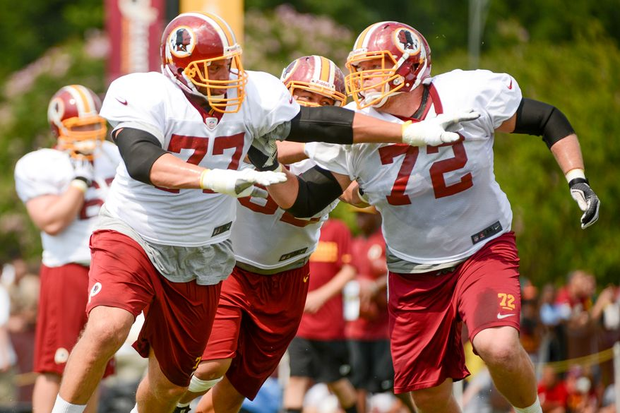 Washington Redskins tackle Tony Pashos (77) and Washington Redskins defensive end Stephen Bowen (72) participate in an offensive line drill during afternoon practice at the Bon Secours Washington Redskins Training Center, Richmond, Va., Tuesday, July 30, 2013. (Andrew Harnik/The Washington Times)