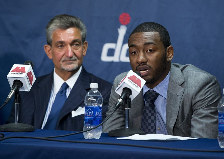 Washington Wizards owner Ted Leonsis, left, looks on as point guard John Wall speaks during a news conference to announce his new contract at the Verizon Center on Thursday, Aug. 1, 2013, in Washington. Wall signed a five-year, $80 million extension to remain with the team. (AP Photo/Evan Vucci)