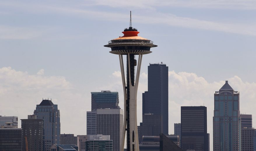 """** FILE ** The top of the Space Needle sports a new coat of orange, called """"galaxy gold"""" when it first appeared 50 years ago atop the structure, as part of the landmark's 50th anniversary celebration on April 23, 2012, in Seattle. (Associated Press)"""