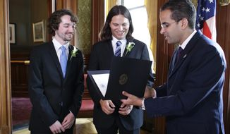 Gary McDowell, left, and Zachary Marcus, center, both of Providence, R.I., are presented with their signed marriage license by Providence Mayor Angel Taveras, right, at City Hall, in Providence, Thursday, Aug. 1, 2013, moments after Taveras presided over the couples marriage ceremony. Gay marriage became legal in Rhode Island and Minnesota at 12:01 a.m. Thursday. (AP Photo/Steven Senne)