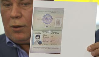 Russian lawyer Anatoly Kucherena displays a temporary document Thursday that allows Edward Snowden to cross the border into Russia. (Associated Press)