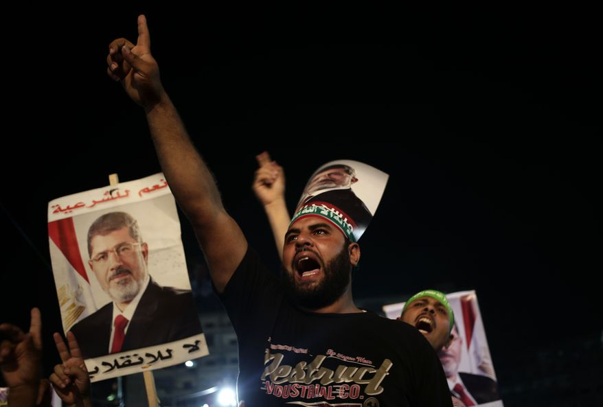 ** FILE ** Supporters of Egypt's ousted President Mohammed Morsi chant slogans against Egyptian Defense Minister Gen. Abdel-Fattah el-Sissi outside Rabaah al-Adawiya mosque, where they have installed a camp and hold daily rallies at Nasr City, in Cairo, Egypt, Friday, Aug. 2, 2013. (AP Photo/Hassan Ammar)