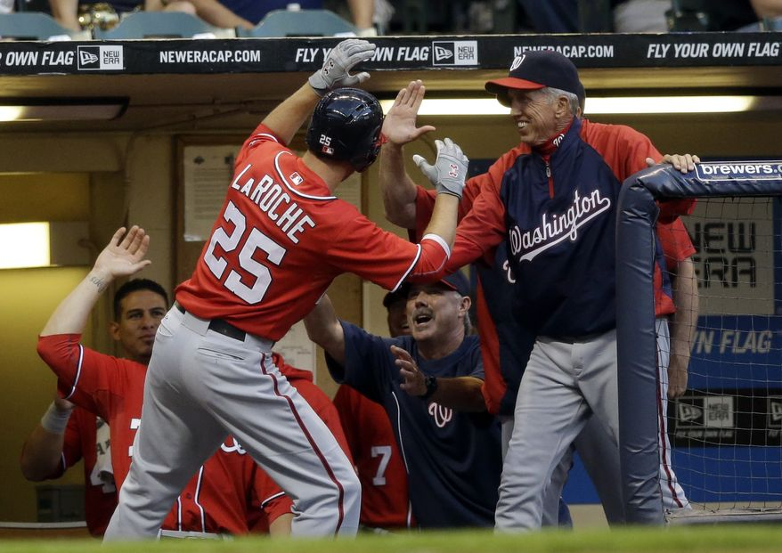 Adam LaRoche returns to the dugout Saturday night after hitting a home run using Jayson Werth's bat. The Washington Nationals beat the MIlwaukee Brewers 3-0. (Associated Press photo)