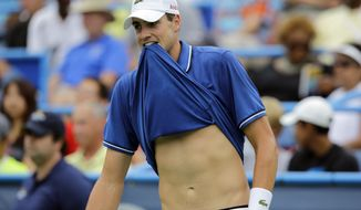 John Isner holds his shirt in his teeth during his match against Dmitry Tursunov, from Russia, at the Citi Open tennis tournament, Saturday, Aug. 3, 2013, in Washington. (AP Photo/Alex Brandon)