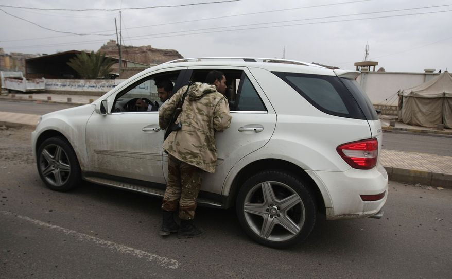 """A Yemeni soldier inspects a car at a checkpoint on a street leading to the U.S. embassy in Sanaa, Yemen, Sunday, Aug. 4, 2013. Security forces close access roads, put up extra blast walls and beef up patrols near some of the 21 U.S. diplomatic missions in the Muslim world that Washington ordered closed for the weekend over a """"significant threat'' of an al Qaeda attack. (AP Photo/Hani Mohammed)"""