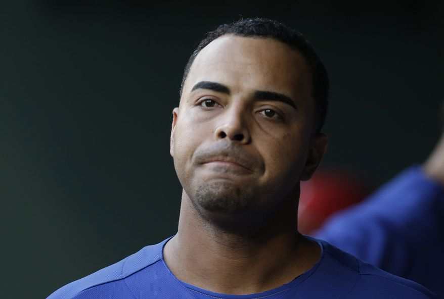 FILE - In this July 21, 2013 file photo, Texas Rangers right fielder Nelson Cruz walks in the dugout during a baseball game against the Baltimore Orioles in Arlington, Texas. (AP Photo/LM Otero, File)