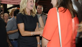 **FILE** Texas State Sen. Wendy Davis (left), famous for her 12-hour filibuster attempt against an anti-abortion rights bill, greets attendees at a fundraiser on July 25, 2013, in Washington. (Associated Press)