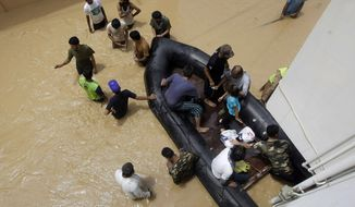 Pakistani soldiers rescue local residents from an area flooded by heavy rains on the outskirts of Karachi, Pakistan, on Aug. 4, 2013. Heavy rains that swept across Pakistan brought down more than 100 homes and caved in a factory wall, killing at least a dozen people in the downpours, officials said. (Associated Press)