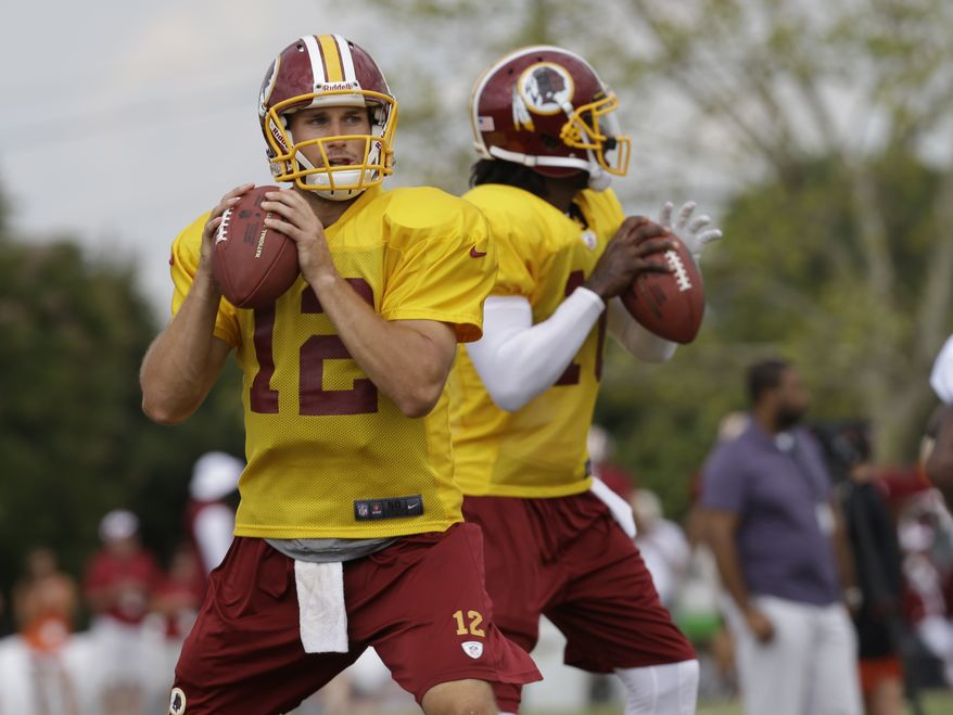 Washington Redskins quarterback Kirk Cousins (12) and teammate Robert Griffin III, right, look for receivers during the afternoon practice at the NFL football team's training camp in Richmond,Va. Monday, Aug. 5, 2013. (AP Photo/Steve Helber)
