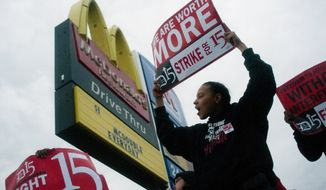 ** FILE ** Fast-food worker Michelle Osborn, 23, of Flint shouts out chants as she and a few dozen others strike outside of McDonald's on Wednesday, July 31, 2013, in Flint. (AP Photo/The Flint Journal, Jake May)