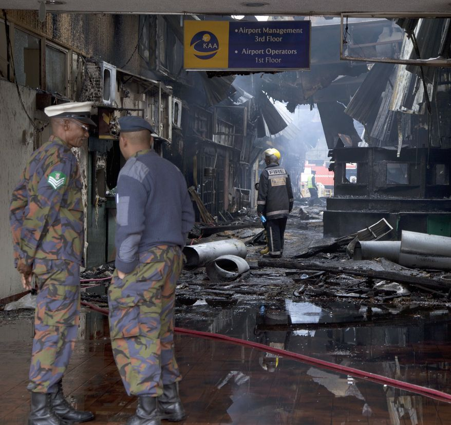 Kenya Airforce personnel view the damage after fire engulf the international arrivals area of Jomo Kenyatta International Airport, Nairobi, Kenya, Wednesday, Aug. 7, 2013. A massive fire engulfed the arrivals hall at Kenya's main international airport early Wednesday, forcing East Africa's largest airport to close and the rerouting of all inbound flights. (AP Photo/Sayyid Azim)