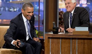 """President Obama smiles as he talks with Jay Leno during a commercial break during the taping of his appearance on """"The Tonight Show with Jay Leno"""" in Los Angeles on Aug. 6, 2013. (Associated Press)"""