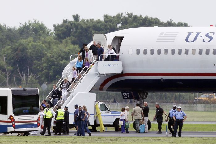 People exit a plane from Ireland that made an emergency landing in Philadelphia because of an unspecified threat on Aug. 7, 2013. (Associated Press)