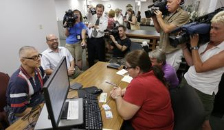 Marcus Saitschenko, left, and James Goldstein obtain a marriage license at a Montgomery County office despite a state law banning such unions, Wednesday, July 24, 2013, in Norristown, Pa. Five same-sex couples have obtained marriage licenses in the suburban Philadelphia county that is defying a state ban on such unions. (AP Photo/Matt Rourke)