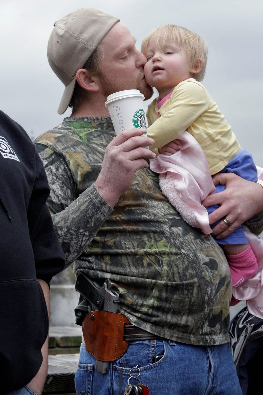 Greg Dement takes daughter Elicia to watch a gun control rally in Seattle. He shows support for Starbucks, which quietly allows gun owners to carry visible weapons. (Associated Press)