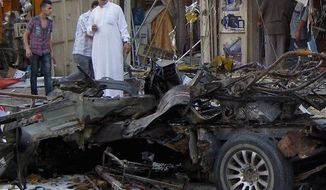 A commercial area of Baghdad is littered with debris Tuesday from a car bombing, one of several in the past week alone. The wave of violence bears the mark of al Qaeda in Iraq. (Associated Press)