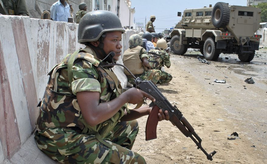 **FILE** African Union peacekeepers take position outside the main U.N. compound, following an attack on it in Mogadishu, Somalia, on June 19, 2013. Al Qaeda-linked militants detonated multiple bomb blasts and engaged in ongoing battles with security forces in an attempt to breach the main U.N. compound in Mogadishu, officials said. (Associated Press)