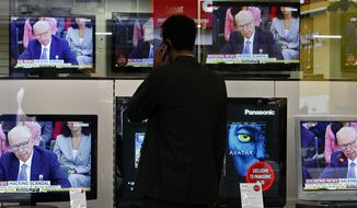 **FILE** A pedestrian using his cell phone stops outside a electronics shop in London on July 19, 2011, by television screens showing Chairman of News Corporation Rupert Murdoch during a select committee on the phone hacking scandal. (Associated Press)