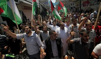 **FILE** Palestinians chant slogans and wave national flags during a rally to mark the Quds Day in Gaza City on Aug. 2, 2013. The International Quds Day was inaugurated by the late Iranian leader Ayatollah Khomeini in 1979 to express solidarity with Palestinians and to oppose Zionism and Israel's control of Jerusalem. Quds is Arabic word for Jerusalem. (Associated Press)