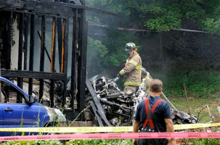 Firefighters work at the scene of a small plane crash, Friday, Aug. 9, 2013, in East Haven, Conn. The multi-engine, propeller-driven plane plunged into a working-class suburban neighborhood near Tweed New Haven Airport, on Friday. (AP Photo/Fred Beckham)
