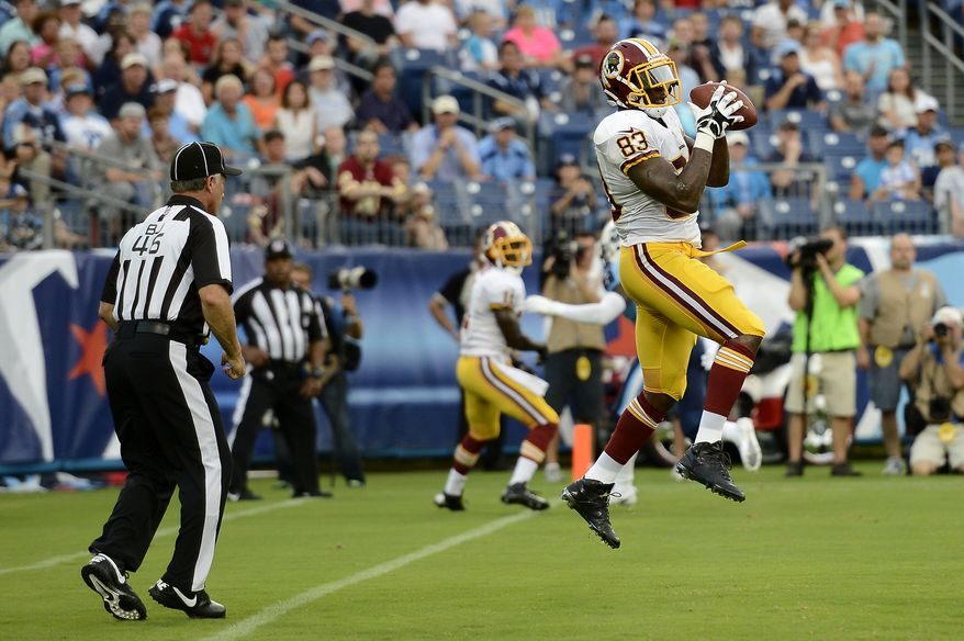 Washington Redskins tight end Fred Davis (83) catches a 3-yard touchdown pass against the Tennessee Titans in the first quarter of a preseason NFL football game on Thursday, Aug. 8, 2013, in Nashville, Tenn. Back judge Perry Paganelli (46) watches the play. (AP Photo/Mark Zaleski)
