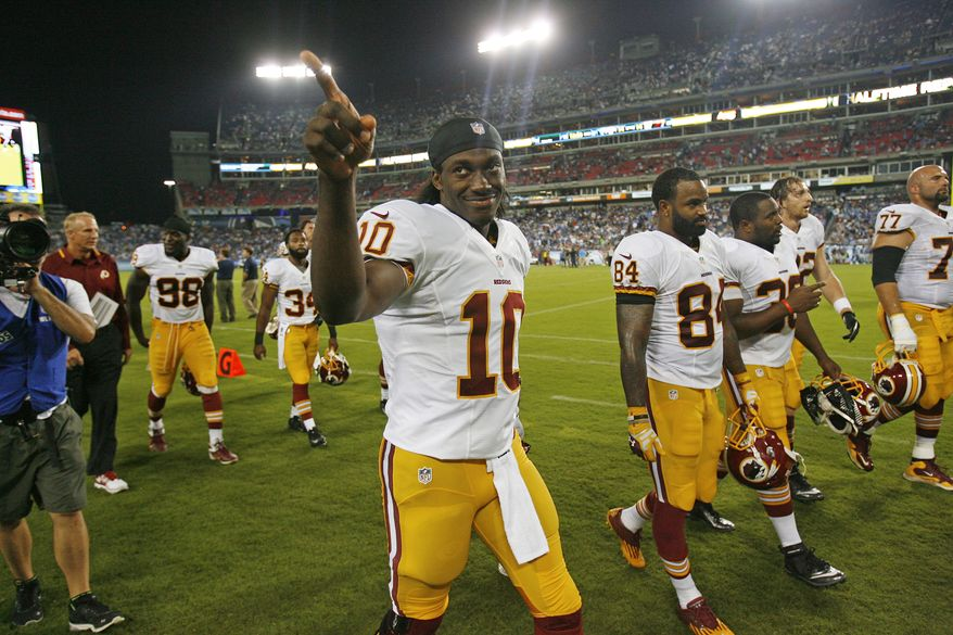 Washington Redskins quarterback Robert Griffin III (10) acknowledges a fan as he walks to the locker room for halftime during a preseason NFL football game against the Tennessee Titans on Thursday, Aug. 8, 2013, in Nashville, Tenn. (AP Photo/Mark Zaleski)