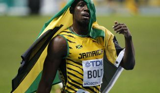 Jamaica's Usain Bolt celebrates after winning gold in the Men's 100-meter final at the World Athletics Championships in the Luzhniki stadium in Moscow, Russia, Sunday, Aug. 11, 2013. (AP Photo/Alexander Zemlianichenko)