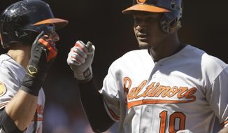 Baltimore Orioles' Adam Jones (right) is congratulated after hitting a three-run home run off San Francisco Giants' Barry Zito in the ninth inning of the Orioles' 10-2 road win on Aug. 11, 2013. (Associated Press)