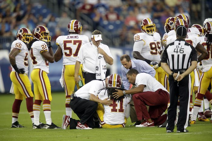 Washington Redskins safety Phillip Thomas (41) is helped after being shaken up in the first quarter of a preseason NFL football game against the Tennessee Titans on Thursday, Aug. 8, 2013, in Nashville, Tenn. (AP Photo/Wade Payne)