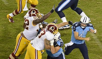 A pass by Tennessee Titans quarterback Ryan Fitzpatrick (4) is blocked by Washington Redskins defensive end Phillip Merling (93) as Merling and Chris Baker (92) pressure Fitzpatrick in the third quarter of a preseason NFL football game on Thursday, Aug. 8, 2013, in Nashville, Tenn. (AP Photo/Mark Zaleski)