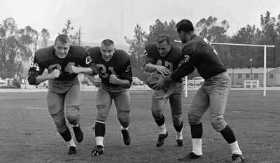 FILE - In this Juy 1961 file photo, Washington Redskins quarterback Ralph Guglielmi hands off to Dick James at the NFL football team's training camp at Occidental College in Los Angeles. Tom Osborne is at left, and Don Besseler is next to him. Teams holding training camp away from home date to the early days of the NFL in the 1920s. The Redskins spent 23 years on the West Coast starting in 1939, including the final 16 at Occidental College. (AP Photo/File)