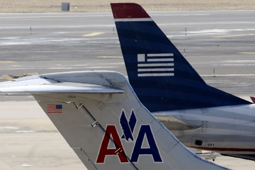 **FILE** American Airlines and US Airways jets prepare for flight at a gate at the Philadelphia International Airport on Feb. 14, 2013. (Associated Press)