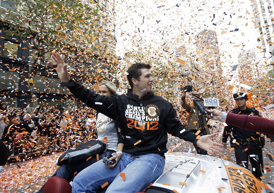 **FILE** San Francisco Giants catcher Buster Posey waves and is showered with confetti during the Giants' baesball World Series victory parade on Market Street in San Francisco, Wednesday, Oct. 31, 2012. (AP Photo/Marcio J. Sanchez)