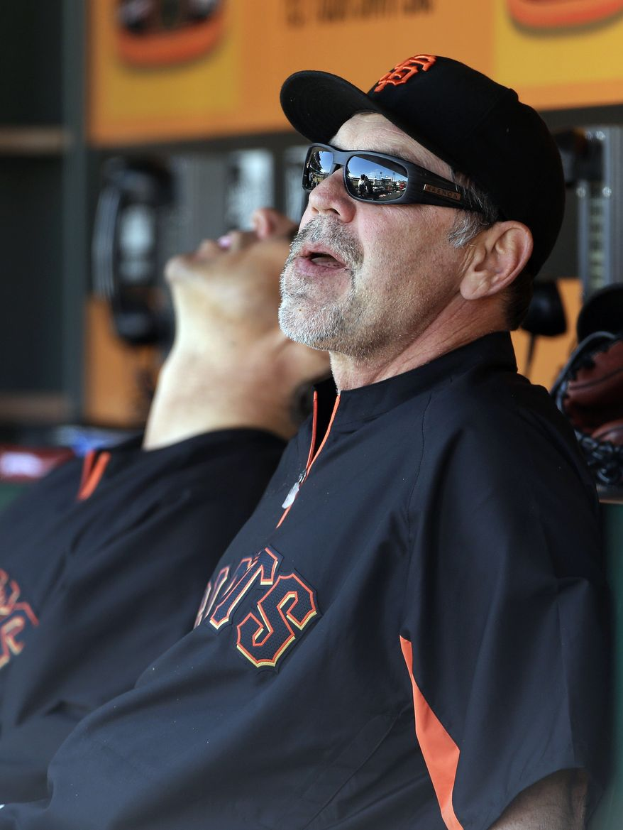 San Francisco Giants manager Bruce Bochy, right, sits with bullpen coach Mark Gardner, left, in the dugout during the eighth inning of their baseball game against the New York Mets, Wednesday, July 10, 2013, in San Francisco. New York won the game 7-2 to sweep a three-game series. (AP Photo/Eric Risberg)