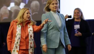 Former Secretary of State Hillary Clinton, center, is escorted to the podium by American Bar Association President Laurel Bellows, left, before addressing the group's annual meeting Monday, Aug. 12, 2013, in San Francisco. Clinton spoke about maintaining the Voting Rights Act and received a medal from the association. (AP Photo/Eric Risberg)