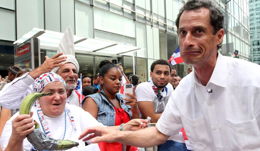 Former Rep. Anthony Weiner reacts after sharing a moment with a spectator and her plantains as he takes part in the Dominican Day Parade on New York's Avenue of the Americas on Sunday, Aug. 11, 2013. (Associated Press) ** FILE **