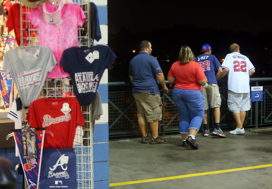 Baseball fans look over a railing at Turner Field near the scene where a man fell 60 feet from the upper deck Monday Aug. 12, 2013. Atlanta police spokesman John Chafee confirmed the death of the man, whose name has not been released. The man fell during Monday night's game between the Atlanta Braves and Philadelphia Phillies. (AP Photo/Atlanta Journal Constitution, Curtis Compton)