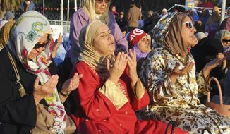 "Tunisian women pray near the Zitouna mosque for the Eid al-Fitr prayer, Thursday, Aug.8, 2013, in Tunis. The prayer is taking place at the so-called ""Departure Sit-in"" on the Bardo square, where people demand the resignation of the ruling moderate islamic Ennahda Party. Tunisians ousted their longtime dictator in January 2011, touching off the Arab Spring uprisings. (AP Photo/Hassene Dridi)"