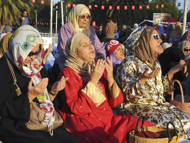 """Tunisian women pray near the Zitouna mosque for the Eid al-Fitr prayer, Thursday, Aug.8, 2013, in Tunis. The prayer is taking place at the so-called """"Departure Sit-in"""" on the Bardo square, where people demand the resignation of the ruling moderate islamic Ennahda Party. Tunisians ousted their longtime dictator in January 2011, touching off the Arab Spring uprisings. (AP Photo/Hassene Dridi)"""