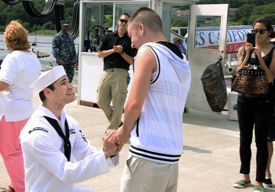 Navy Petty Officer 2nd Class Jerrel Revels proposes Monday to his boyfriend, Dylan Kirchner, as the USS New Mexico is docked at Groton, Conn. Gay spouses of service members and Pentagon civilians will begin receiving military benefits by Sept. 3. (Associated Press)