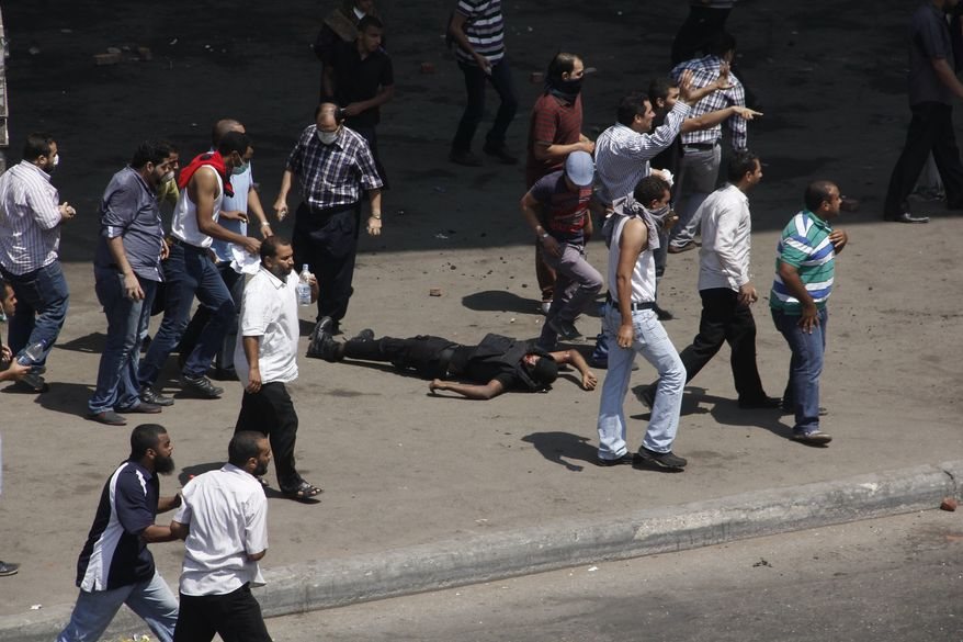 A member of the security forces lies on the ground as protesters gather, and one strikes him with his shoe, after his police vehicle was pushed off the 6th of October bridge by protesters, near the largest sit-in by supporters of ousted Islamist President Mohammed Morsi in the eastern Nasr City district of Cairo, Egypt, Wednesday, Aug. 14, 2013. Egyptian police in riot gear swept in with armored vehicles and bulldozers Wednesday to clear the sit-in camps set up by supporters of the country's ousted Islamist president in Cairo, showering protesters with tear gas as the sound of gunfire rang out. (AP Photo/Aly Hazzaa, El Shorouk Newspaper)