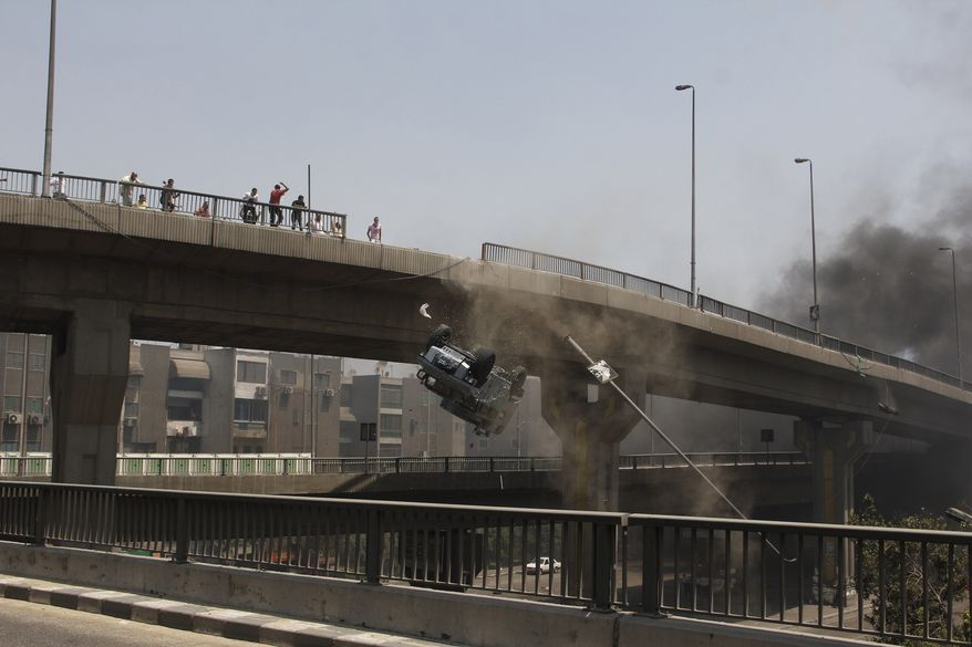 A police vehicle is pushed off of the 6th of October bridge by protesters close to the largest sit-in by supporters of ousted Islamist President Mohammed Morsi in the eastern Nasr City district of Cairo, Egypt, Wednesday, Aug. 14, 2013.  Egyptian police in riot gear swept in with armored vehicles and bulldozers Wednesday to clear the sit-in camps set up by supporters of the country's ousted Islamist president in Cairo, showering protesters with tear gas as the sound of gunfire rang out. (AP Photo/Aly Hazzaa, El Shorouk Newspaper)