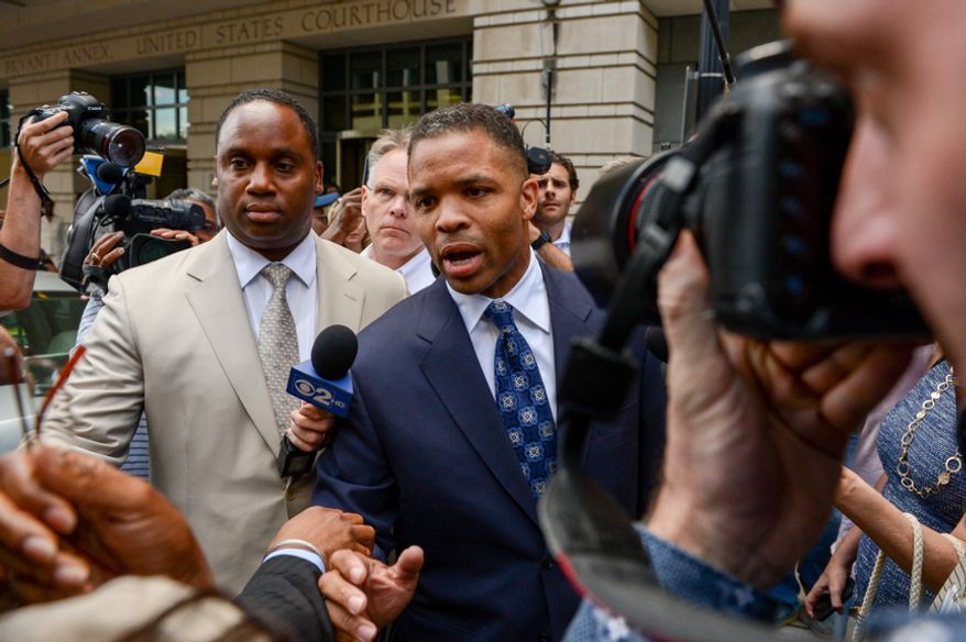 ** FILE ** Former Illinois Rep. Jesse Jackson Jr. (center) leaves a D.C. federal court on Aug. 14, 2013, after being sentenced to 30 months in prison for stealing money from his own campaign. (Andrew Harnik/The Washington Times)