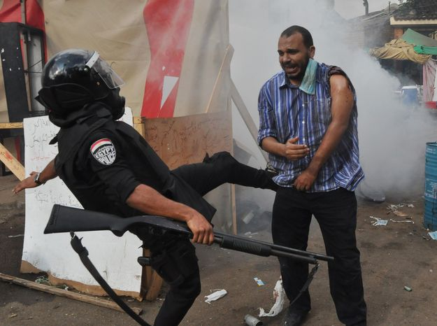 An Egyptian security force kicks a supporter of ousted Islamist President Mohammed Morsi as they clear a sit-in camp set up near Cairo University in Cairo's Giza district on Aug. 14, 2013. Egyptian police in riot gear swept in with armored vehicles and bulldozers to clear the sit-in camp and the other encampment set up by supporters of Morsi, showering them with tear gas as the sound of gunfire rang out. (Associated Press)