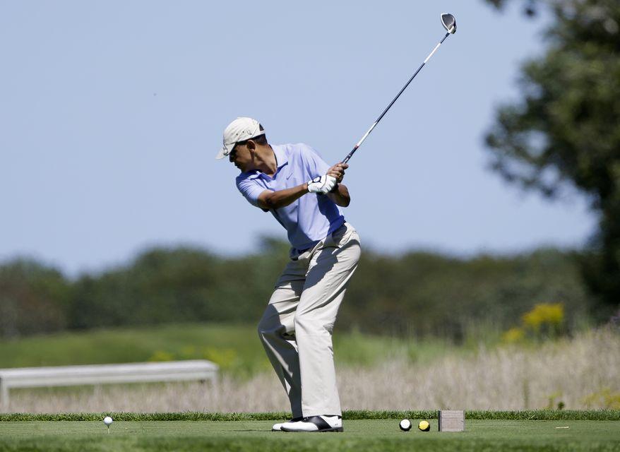 President Barack Obama tees off while golfing at Vineyard Golf Club in Edgartown, Mass., on the island of Martha's Vineyard Wednesday, Aug. 14, 2013. (AP Photo/Steven Senne)