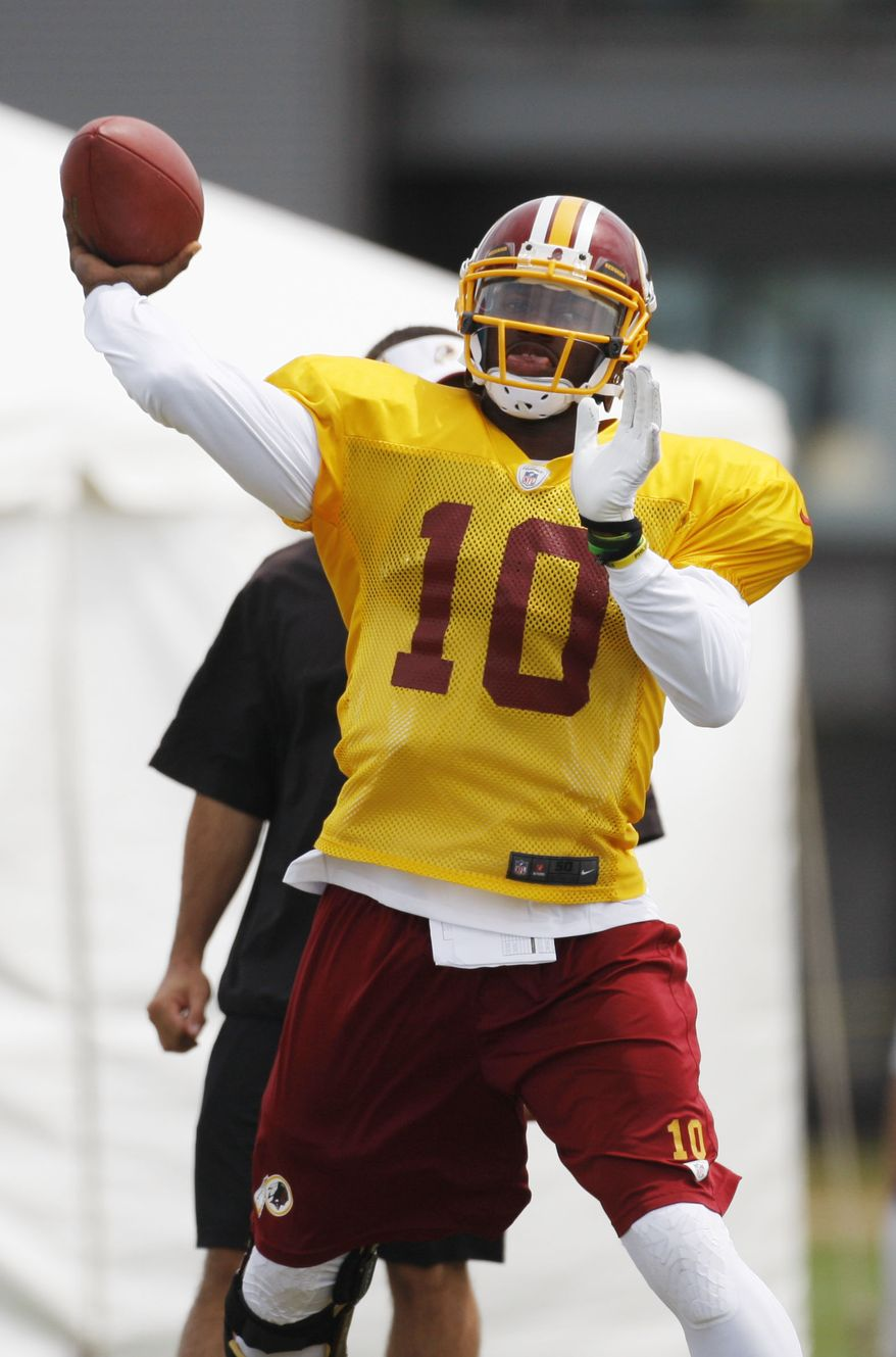 Washington Redskins quarterback Robert Griffin III works on passing drills during the practice at the NFL football team training camp in Richmond, Va., Wednesday, Aug. 14, 2013. (AP Photo/Richmond Times-Dispatch, Daniel Sangjib Min)