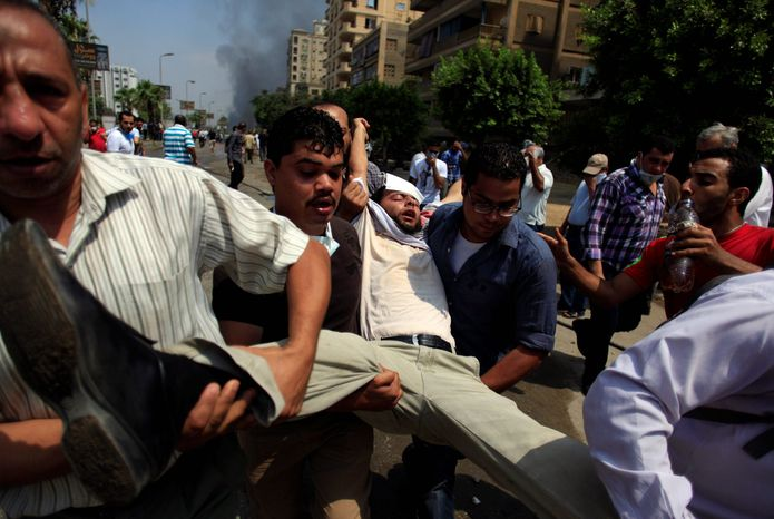 """Mass Violence: Supporters of Mr. Morsi carry a wounded man through the mayhem. As the Egyptian military appeared to claim more power, a White House spokesman warned that """"The world is watching."""""""