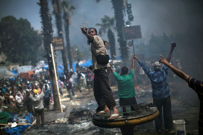 Facing a Goliath: A supporter of ousted Islamist President Mohammed Morsi shoots a slingshot against Egyptian security forces during clashes in Cairo. Police in riot gear swept in with armored vehicles and bulldozers to clear two sprawling encampments. Gunfire rang out as protesters were showered with tear gas. (Associated Press photographs)