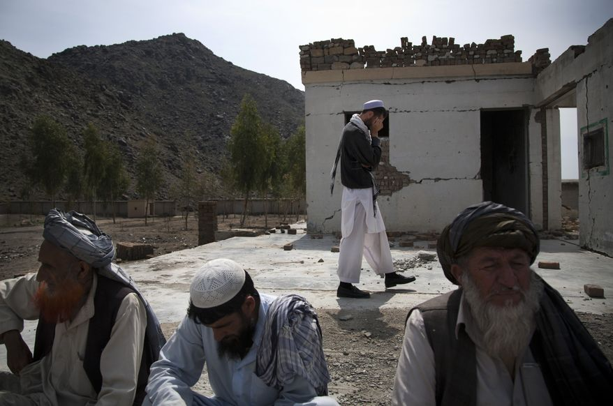 **FILE** Afghan men sit among the debris of their destroyed school in the village of Budyali in the Nangarhar province of Afghanistan on March 19, 2013. Taliban militants attacked the nearby district headquarters in July 2011, then took refuge in the school. The Afghan National Army requested help from coalition forces, who responded with drones, fighter jets and rockets, leaving the school destroyed, according to village elders. (Associated Press)