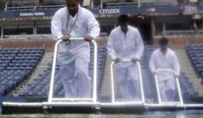 **FILE** Workers squeegee water from the court in Arthur Ashe Stadium as rain fell at the 2012 US Open tennis tournament, Wednesday, Sept. 5, 2012, in New York. (AP Photo/Mike Groll)